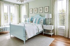 Blue and green farmhouse bedroom is furnished with a blue French wood bed dressed in white and green bedding complemented with blue striped pillows.