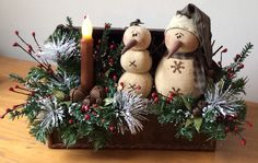 This elongated vintage chest is filled with two prim snow folk.  Embellished with pine, frosted Ming, glittery leaves, rusty jingle bells, lacquered berries and a wax dipped, battery operated flicker candle.