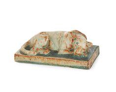 """ALEXANDRE BIGOT (Céramiste 1862-1927) et Paul JOUVE (Sculpteur 1880-1973) Sculpture en grès, représentant une lionne couchée reposant sur une terrasse parallélépipédique, émaux verts, bruns et verts jaspés de bleu. Numérotée en creux """"BS64"""". Haut. 6 cm - Long. 15,5 cm - Larg. 7,5 cm"""
