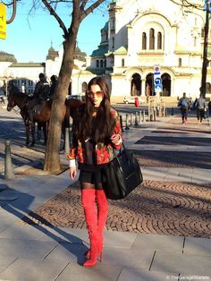 Gema wearing a stunning pair of red suede thigh high boots paired with a short black skirt.