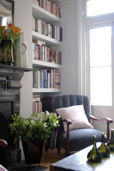white bookshelves, black fireplace. beautiful chair & accessories.