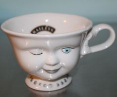 Bailey's Irish Cream produced this winking teacup or mug, which was decorated by actress Helen Hunt for the Los Angeles Youth Network. They feature Hunt's signature on the back. The girl on the cup has a pale blue eye and a silver necklace and eyebrows and bow are unpainted.  #bailleys #helenhunt #winking