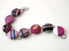 """This recycled necktie bracelet is made using 8 reclaimed men's neckties in Pink, Fuschia, Gray and Black designs featuring stripe, paisley, plaid and geometric patterns.    The silvertone metal bracelet is 7 ½"""" long and features 8 fabric covered ¾"""" flatback buttons and a box clasp."""