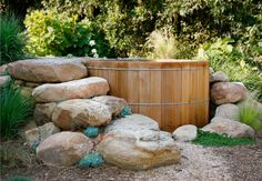 Up-close view of the semi-sunken hot tub, stone steps on left, planted w/ succulents