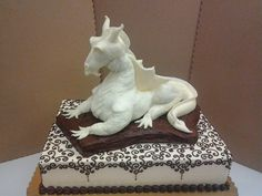White Dragon - The dragon is made of rice krispie treats covered in white modeling chocolate. He is resting on a half sheet cake. This cake was for a bridal shower. The bride is having a medieval wedding.