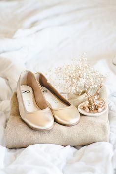 Suéter dourado e sapatilha dourada em cima da cama branca com outros elementos dourados (acessórios e porta anel de cabeça de cervo).