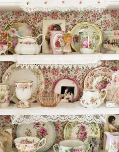 Vintage mismatched china cups, creamers and plates look gorgeous on shelves backed with floral wallpaper.