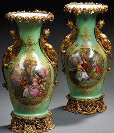 A pair of gilt~Bronze Mounted~Paris Porcelain vases with stands~Each baluster-form~With grapevine collar to neck Green ground~Handles cast as grotesques  Reserve polychrome hand painted with a scene of courting couples~Removable~Reticulated stand with further grapevines~Heavily gilded~Origin France circa 1820-1830