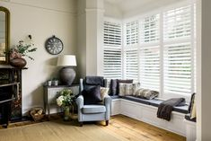 A timeless living room with modern farmhouse decoration. The large boxed bay window dressing with solid white shutters is a space saving solution surrounding the bay window seat.