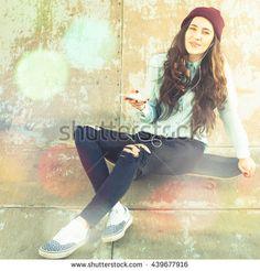 Hipster skateboarder girl with skateboard outdoor sitting at skate-park. Vintage image. Old school. Skatebord at city street. Cool, Funny Tenager. Halfpipe. Skateboarding at Summer. Schoolgirl