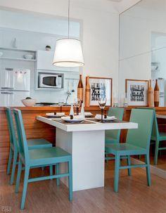 """Na bancada que faz a integração à sala, um bem-vindo toque de aconchego: """"A madeira quebra a frieza do branco, aquecendo o visual"""", diz Cecilia Belluci. Em vez de colocar banquetas, comuns em cozinhas americanas, a arquiteta optou por uma mesa encostada no móvel. """"Sem atrapalhar a passagem, esse item acomoda mais gente do que um balcão e o conforto é maior."""" Cadeiras: de madeira com acabamento laqueado"""