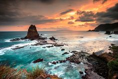 Papuma Beach, East Java | The wind blows the ocean, the ocean crashes against towering rock formations.