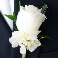 Stunning boutonniere for a groom or best man. White rose paired with a collar of white hydrangea accented with a sprig of veronica and green ruscus.