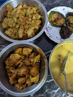 (clockwise from bottom right) Dal, potato-cauliflower curry, potato-drumstick-poppy-seed-paste side, brinjal fry