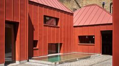 A cluster of red metal-clad volumes are arranged around a secluded courtyard at Henning Stummel's self-designed home in west London.