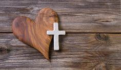 Picture of wooden background - olive heart and white cross for an obituary notice.