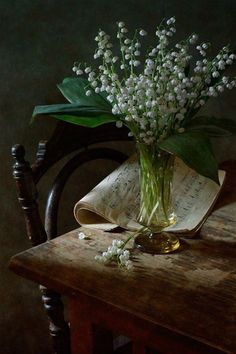 Lily Of The Valley - nikolay-panov. still life with bouquet of lily of the valley in yellow glass vase and vintage music book on wooden table, old chair near table is illuminated by daylight