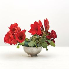 Red Punch Arrangement: For the Middle Ground, add rose foliage and then tuck in affordable fillers such as carnations and tea roses, placed low in the arrangement.