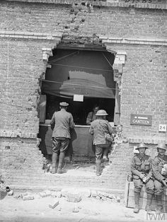 WWI, 27 June 1917; Canteen counter of the 17th Division erected in hole in wall of building made by shell. Blangy-sur-Ternoise. ©IWM Q 5531