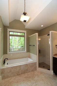 A large soaking tub rests at the center of this classic his and hers master bath. The tile shower and private toilet room stand on each side of the square tub, followed by his and hers vanities. The vaulted ceiling opens up the bathroom, with a large picture window for natural light.
