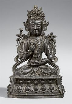 A bronze figure of a bodhisattva (pusa). Ming dynasty A bronze figure of a bodhisattva (pusa), seated in meditation (padmasana) on a double lotus throne, the right hand is raised in mudra, the left hand holds a small round object, attributes are supperted by leafy branches at the shoulders, the figure is adorned by an elaborate crown, ear plates and necklaces. Traces of gilded lacquer. Ming dynasty. Height 31.3 cm