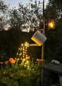 Watering can with fairy lights in the garden.