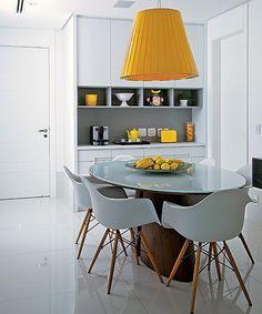 """Na sala de almoço, o branco predomina desde o piso de technostone. """"Brinquei com acessórios amarelos para alegrar o ambiente"""", diz a arquiteta Ligis Resstom. A mesa com tampo de vidro e base de madeira, de Sergio Fahrer, ganhou o pendente de tecido"""