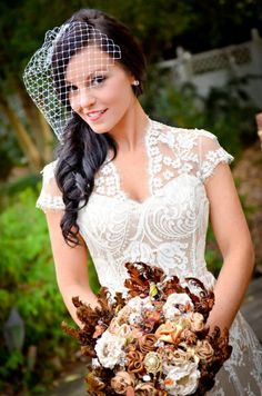 Hair half up half down w/ birdcage veil attached by chiffon/rhinestone flowers in the back (behind ear mainly)