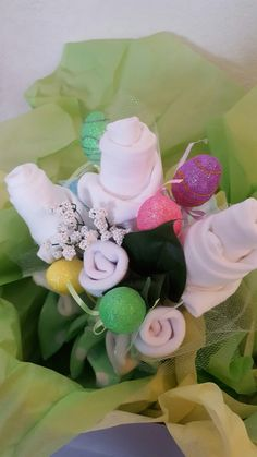 Oneies bouquet  Oneies, socks,baby washcloths.  Very fun and semi easy to make.