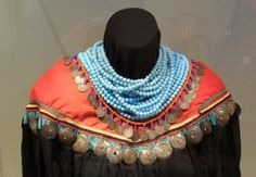Women and girls often wore necklaces strung with dimes or quarters, a trend dating back to the 2nd Seminole War era. The cape is ornamented with 31 tin disks made to look like the more costly silver broaches.