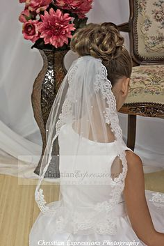 This first communion mantilla features delicate scalloped lace with scattered pearls. this first communion veil includes an attached comb.