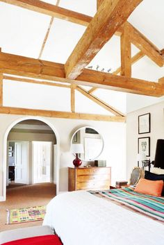 Exposed ceiling beams in this white bedroom with round mirrors and colorful throw blanket