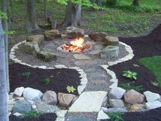 The boulders placed around this fire pit are used for seating as the pit itself is at ground level. A level surface is key for this fire pit installation. There is a gradual pitch inside the fire pit that allows for water runoff and a French drain has been installed under the fire pit for water removal.