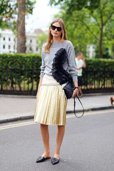 Victoria Sekrier wearing grey ruffle detail jumper and gold pleated skirt by Dries Van Noten. LC:M 2016 Street Style. London.