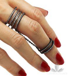 Multiring wykonany ze srebra próby 925, rodowany o kolorze ciemnym, oksydowany, wysadzany cyrkoniami o szlifie brylantowym. Szerokość wzoru to około 1,5 cm. Drugi pierścionek regulowany, o szerokości około 0,5 cm. Obrączki połączone łańcuszkami. Wzór można nosić na jednym palcu lub na palcach sąsiadujących. Model uwielbiany przez gwiazdy.