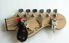 Hello guitar lovers!!!! Turn some heads with this amazing looking key holder. Designed in the style of a Stratocaster, one of the most iconic and easily recognized guitars ever made!!!  The face of the rack is made from two tone acrylic with a wood back and comes with actual chrome guitar tuning pegs that just adds a fantastic look of realism to a unique key holder.  Guitar gunslingers, metal maniacs and axe wielding guitar gurus everywhere will truly appreciate one of these little beautys…