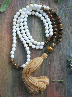 Mala necklace made ​​of 8 mm - 0.315 inch shell and tiger eye gemstones. Together they count as 108 beads. The mala is decorated with hematite and the guru bead is a faceted quartz stone - look4treasures on Etsy