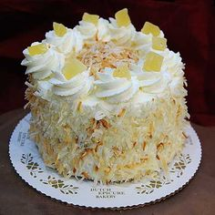 Pina Colada Cake : Three layers of vanilla sponge cake are filled with rum flavored whipped cream and pineapple, covered with toasted coconut and garnished with dried pineapple.