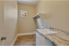 Laundry room with ornate countertops & wash sink.