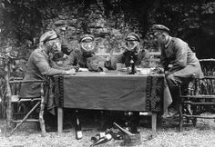 German NCOs from Infanterie-Regiment No. 358 pose for the photographer as if they were drinking wine, feasting on gherkins and playing cards while wearing gas masks.