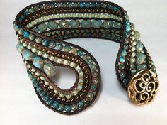 Aqua calsilica gemstone, Czech glass, brown leather and a brass button combine in this beautiful cuff bracelet.