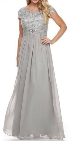 Show off your style in this beautiful and modest silver formal dress. Great as a mother of the bride, this long chiffon dress features a lace top with short cap sleeves, a modest round neckline and a brooch around the empire waist. A great dress for many different occasions!  Designer: Juliet Item number: 519 Material: chiffon. 100% polyester. Fully lined. Soft cup padded inserts. Back zipper. Approximately 58 inches from top of shoulder to hem.      Size S M L XL 2XL 3XL 4XL   Bust 34 36 38…