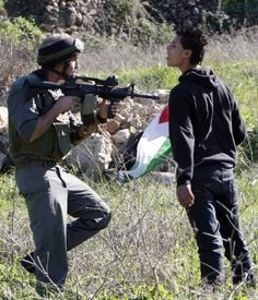 Who's the coward here? The man pointing the gun at the kid or the kid facing the man with a gun? You tell me. Long live Palestine.