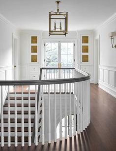 Metal grill front cabinets mounted above white built-in cabinets flank French balcony doors in this exquisite second floor l… Iron Staircase Railing, Staircase Storage, White Staircase, Luxury Staircase, Railings, Interior Balcony, Mansion Interior, French Balcony, Metal Grill