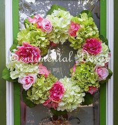 This hydrangea wreath features white hydrangeas, spring green hydrangeas, pink peonies, garden roses, and coral accent flowers. This is