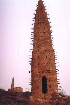 Two minarets in traditional West African style with typical bundles of deleb palm wood embedded in the walls