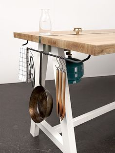 Wooden dining table with integrated gas burners designed for collaborative meal production.