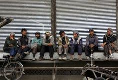 Afghan labor workers wait for customers in Kabul, Afghanistan, Sunday, April, 19, 2015. (AP Photo/Rahmat Gul)