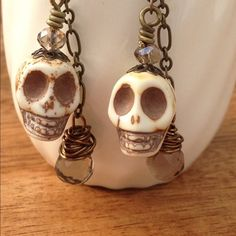 """Skull earrings Get ready to celebrate Dia de Los Muertos in style! Tear drop crystal wire wrapped with small crystal bead on skull head. Antique brass ear hooks. Measures approx 2"""" from the ear hook. Handmade with lots of love by me❤️ Chula Art Jewelry Earrings"""