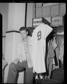 Ted Williams (in civvies) in front of his locker at Fenway Park after his return from military service in Korea. He is holding up his familiar #9 jersey.: 1953